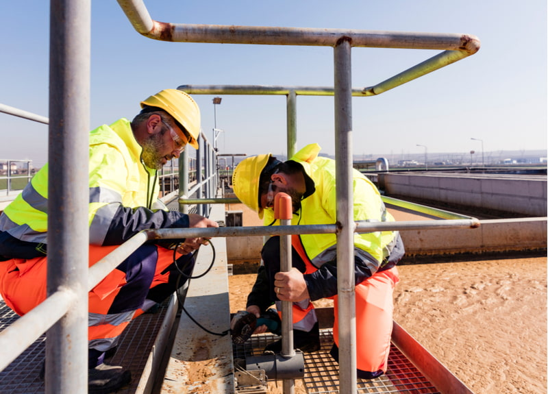 Workers on site of wastewater treatment plant fixing sensors