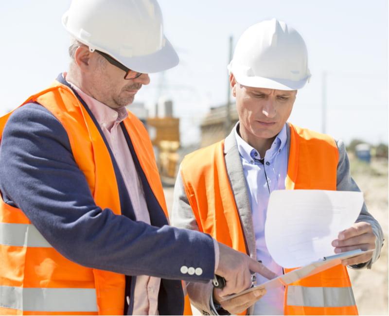 Engineers examining documents on clipboard