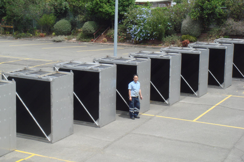 Man standing in front of oil separators outside